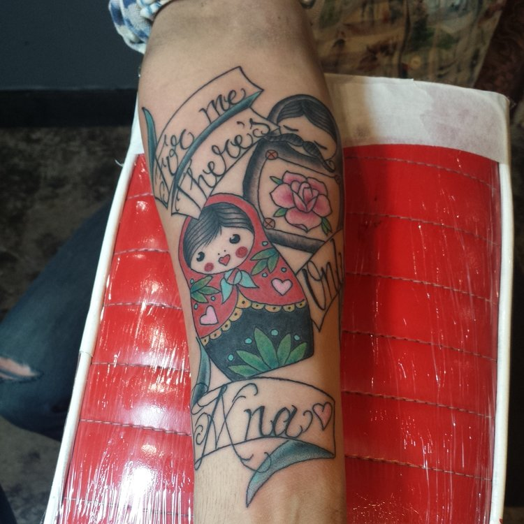 Russian nesting dolls with banners and letting. Forearm half sleeve color tattoo.