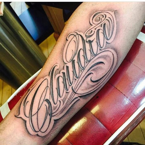Black and gray Claudia script lettering on the forearm tattoo.