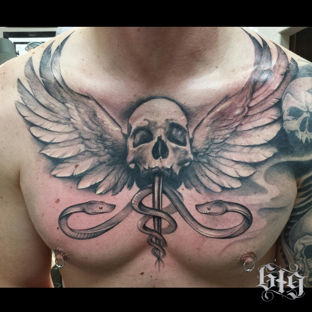 Skull with feathered wings and snakes. Chest piece black and gray tattoo.