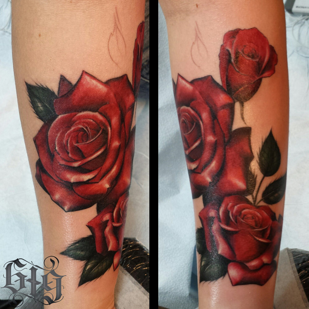 Red roses with green leaves. Forearm half sleeve tattoo.