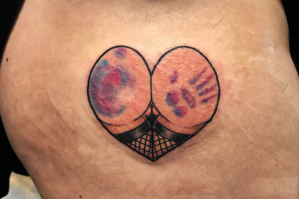 Heart butt tattoo wearing thigh high stockings and a hand print in color.