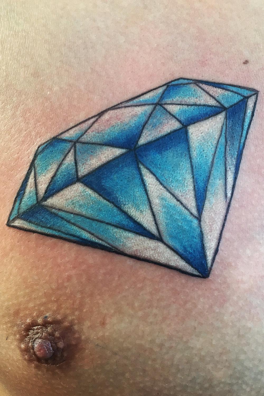 Blue diamond tattoo on upper chest.