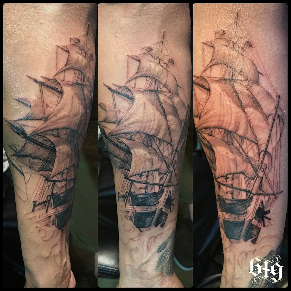 Realistic clipper ship sailing the high seas black and gray tattoo in progress.