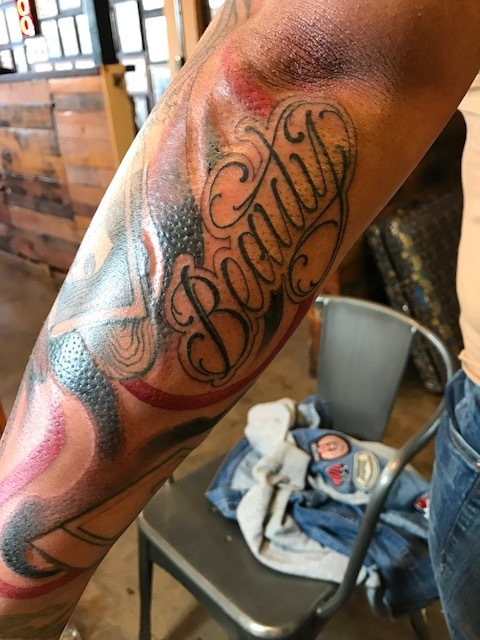 """Beauty"" beautifully written in black and gray with a swirl of red white and blue on forearm. Full sleeve tattoo"