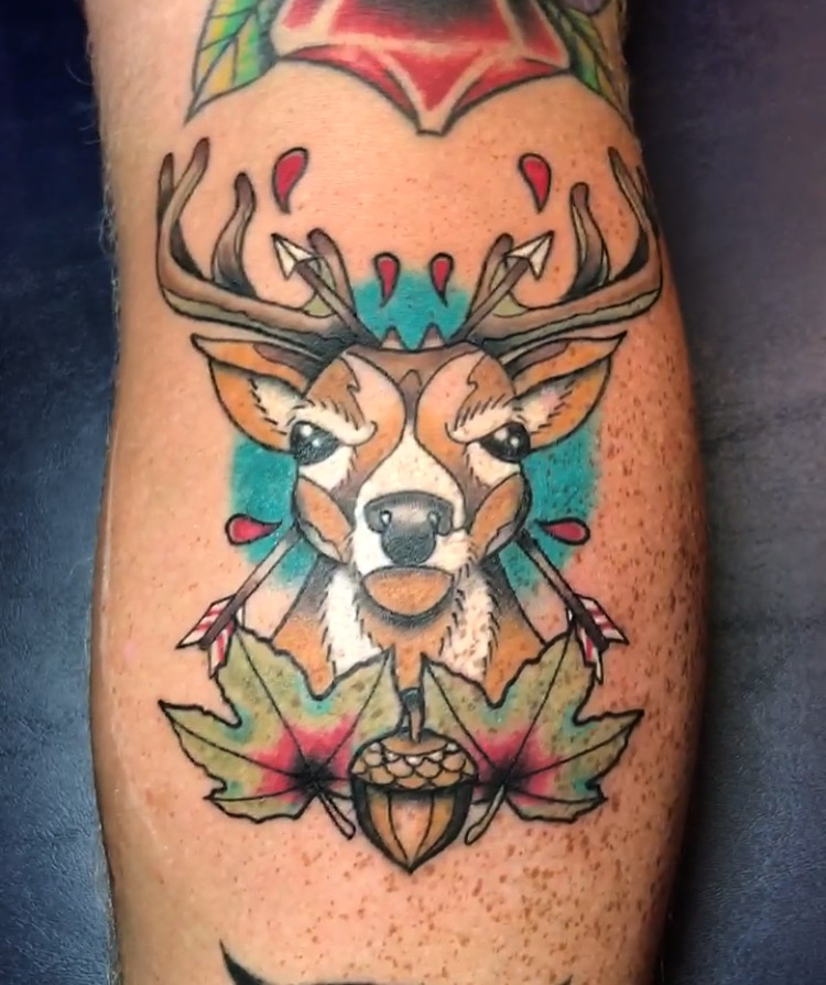 Neotraditional tattoo in color of a buck head arrows, acorn and maple leaf.