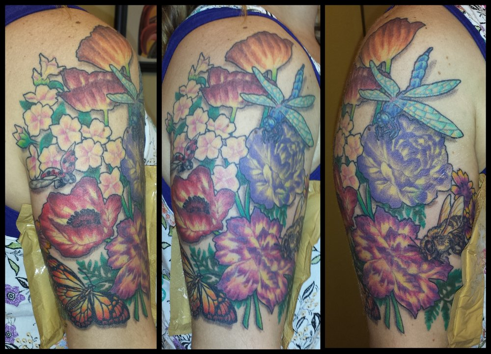 Wild flowers in watercolor with poppies, a butterfly and dragon fly. Upper arm half sleeve color tattoo.