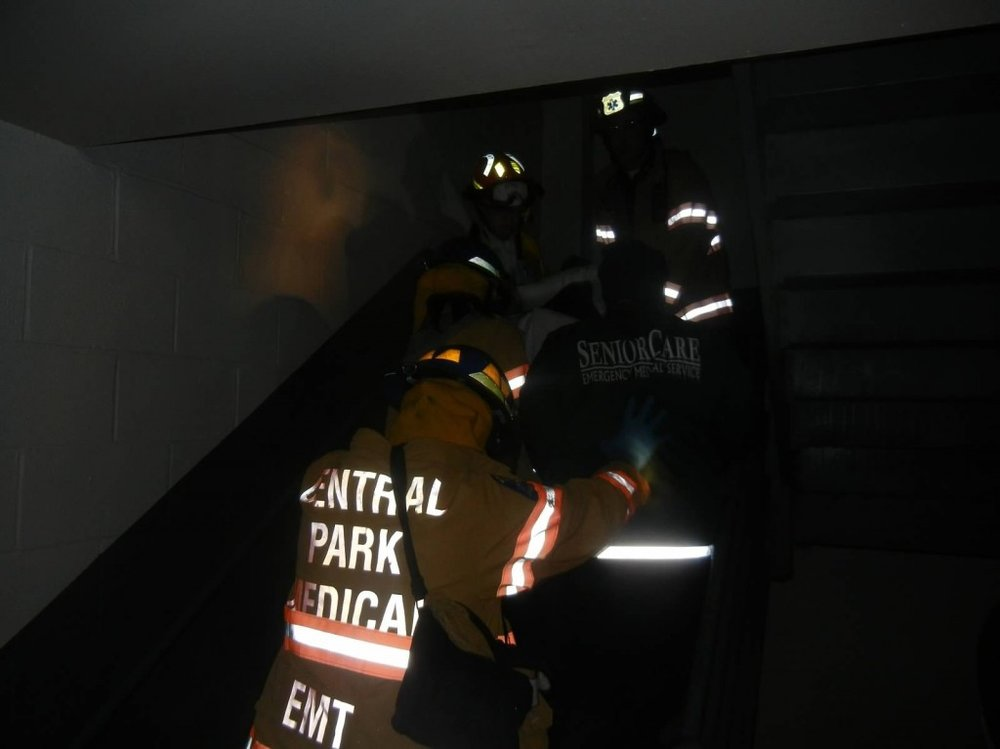 CPMU members evacuate a patient down a dark staircase at Horizon Nursing Home in Far Rockaway