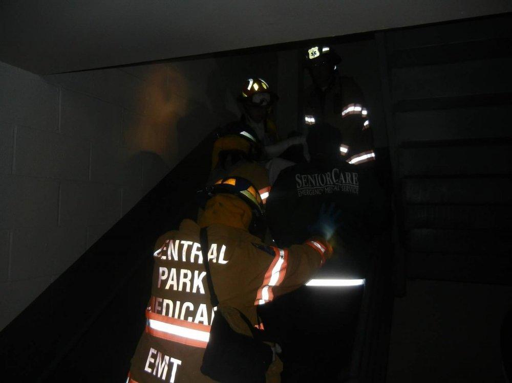 CPMU members evacuate a patient down a dark staircase at Horizon Nursing Home in Far Rockaway