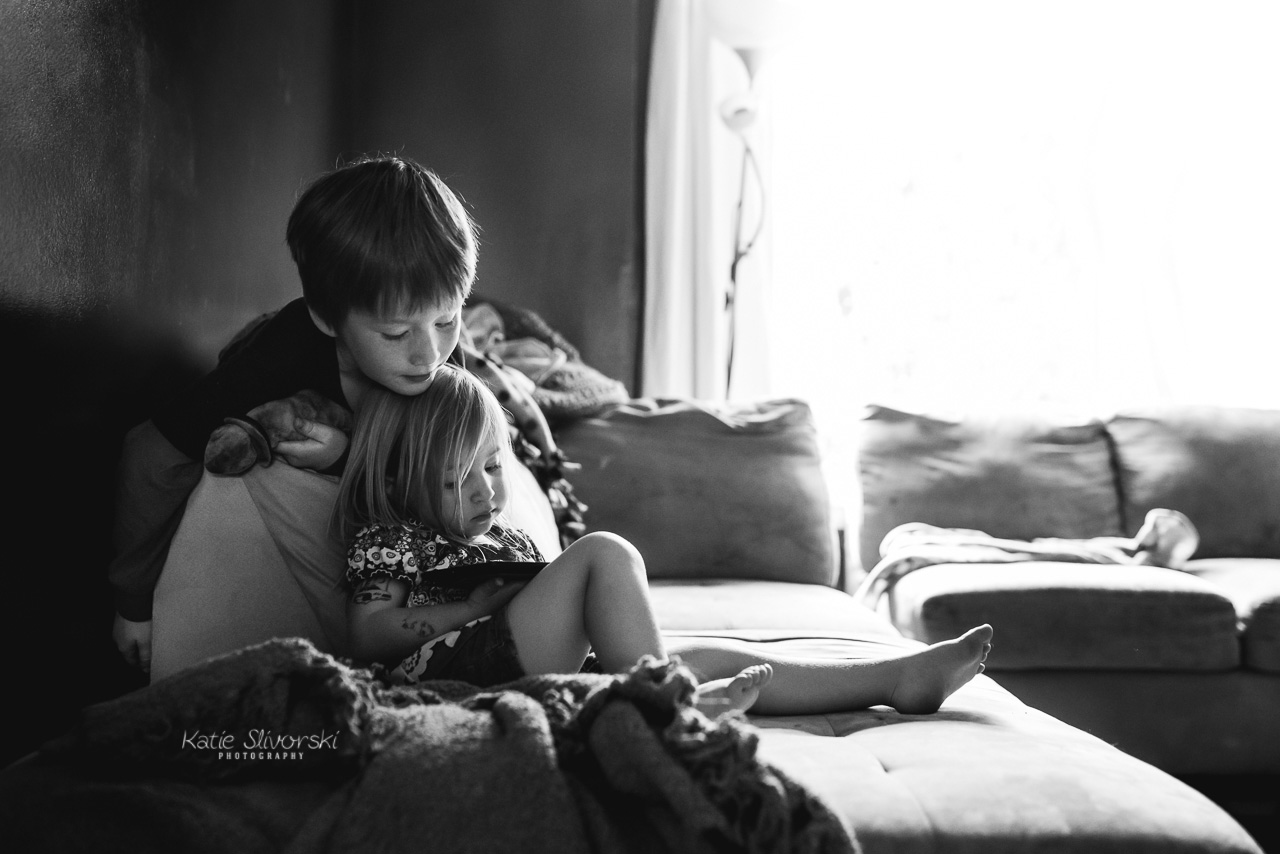A family photography image of kids playing with a tablet.