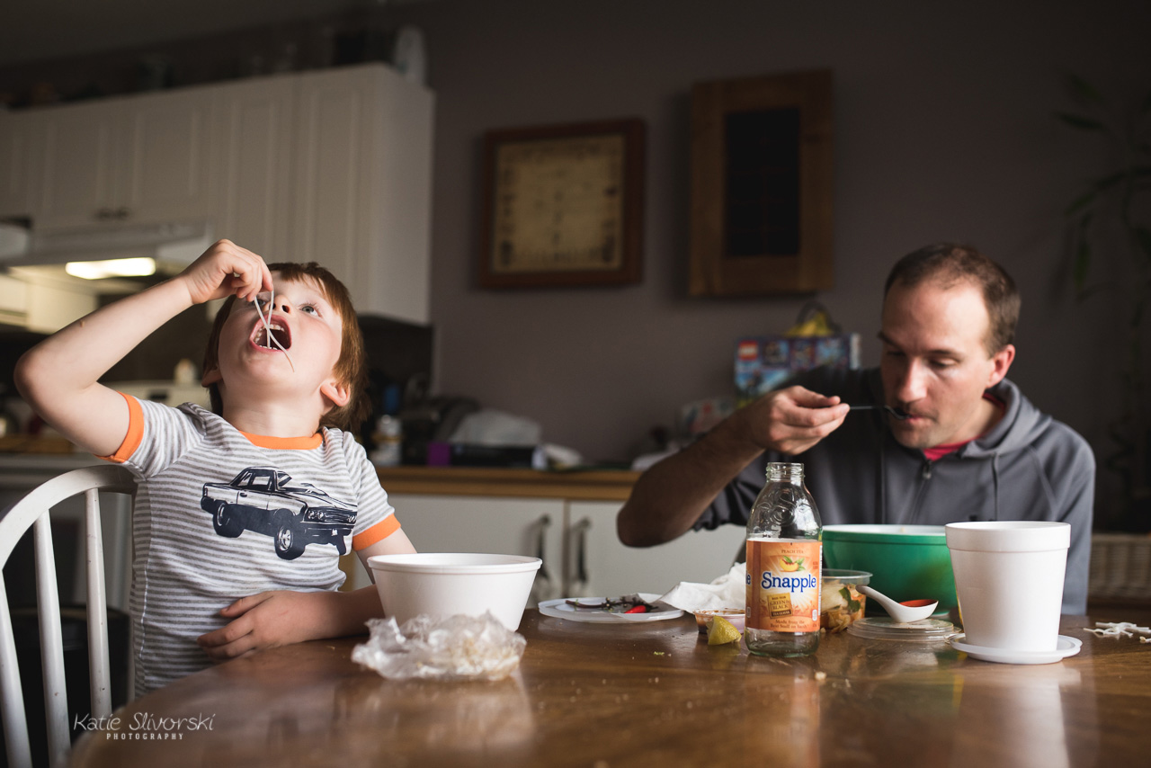 A family photography image of a child eating soup.