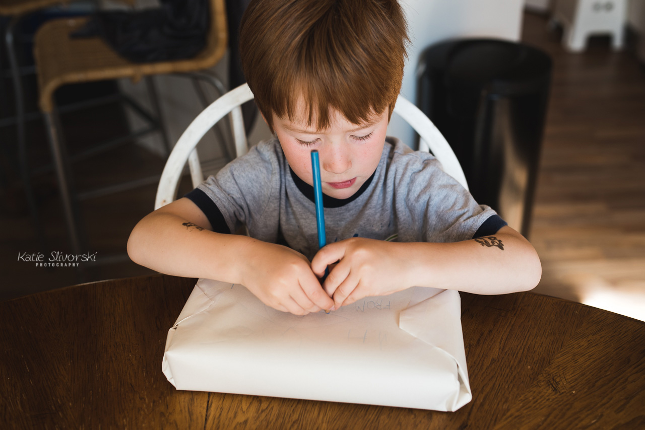 A photo of a boy writing on a package