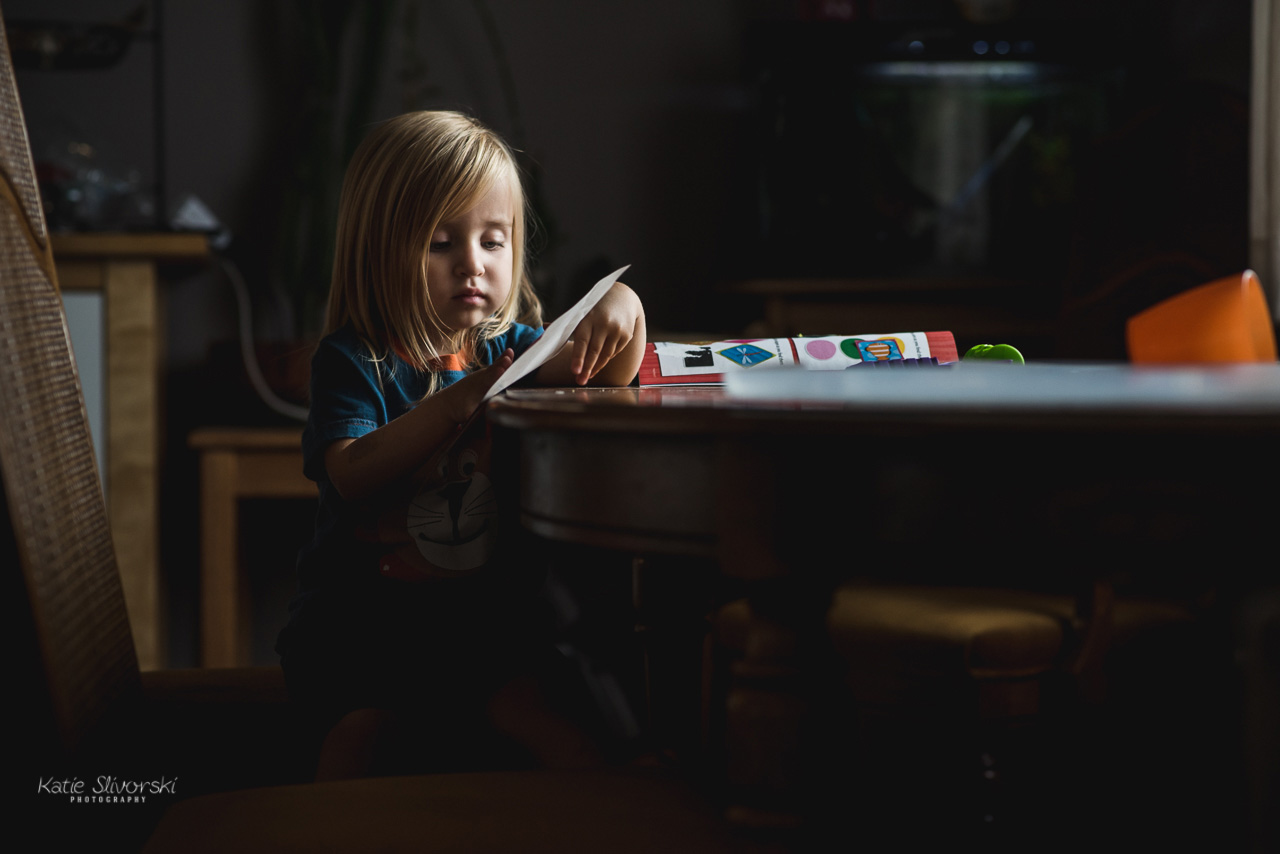 Lifestyle photographer image of girl putting stickers on a book