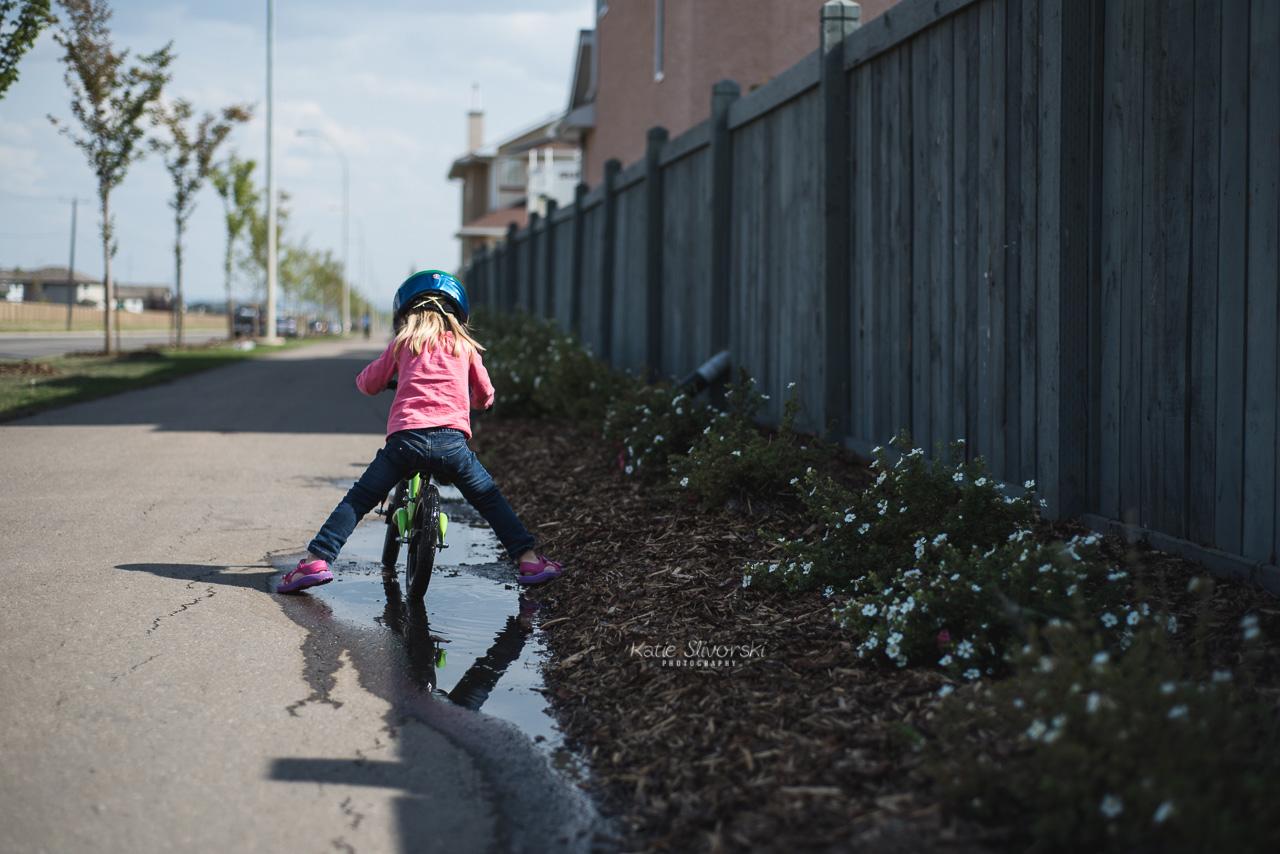 child riding balance bike over a puddle