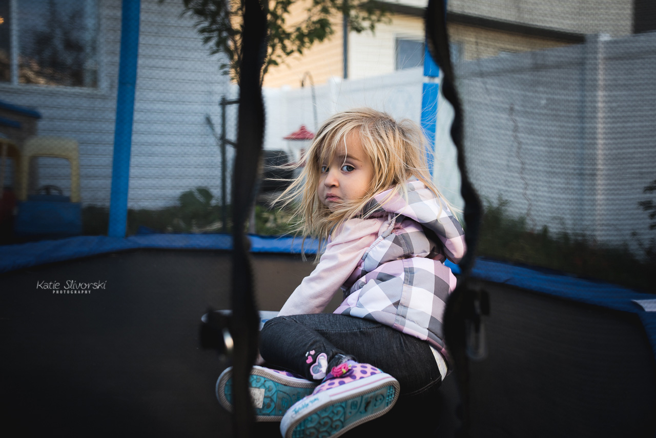 Family photographer image in Edmonton of child jumping on trampoline