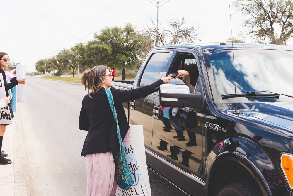 Giving literature to people driving by. / 2/13/16 / SeaWorld / San Antonio, TX