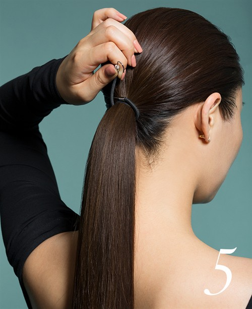 Once completely dry, pull your hair into a low, centred ponytail. Securing with a hair bungee.