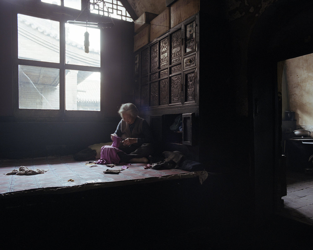 Sitting on the warm kang near the light. The grandmother is embroidering. The children will do their home work here, while other grown ups use the kang as kitchen to prepare the food.