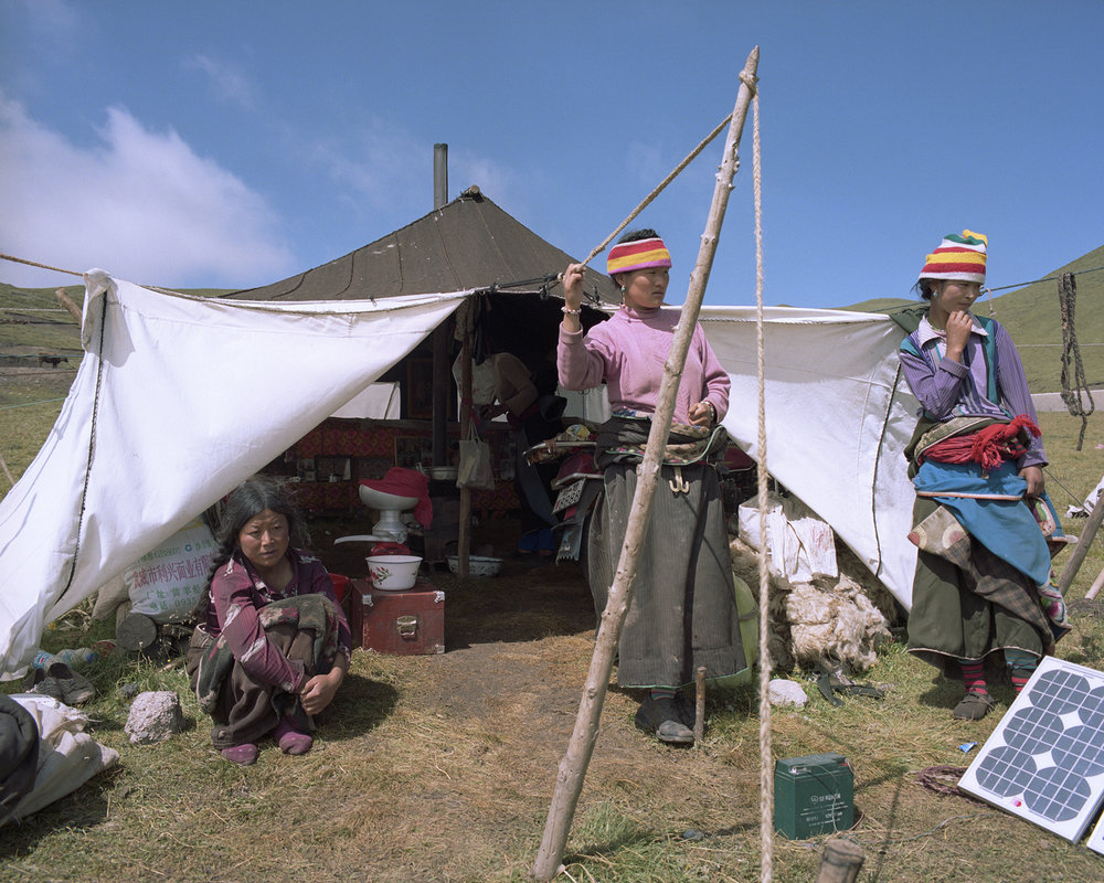 2007-Qinghai -Nomad women at their tent. Many of the men will be deeper into the mountains with most of the yak. Solar power provides electricity for the butter separator and for the mobile phones to keep in contact with each other.