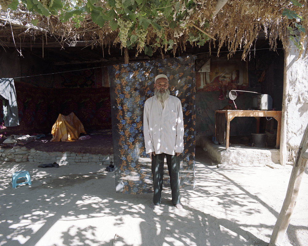 2007 Xinjiang - grape farmer and grandfather at his home. In the back his grandson in his cradle.