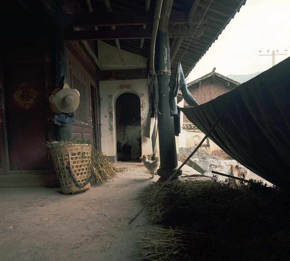 2008 Yunnan - pea harvest laying out to dry on a  porch off the courtyard of another 'big house'.