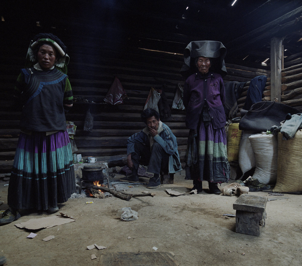 2010, in the vicinity of Lugu Lake - a Yi family in their home. This is their daily costume. No tourists come this far into the mountains.