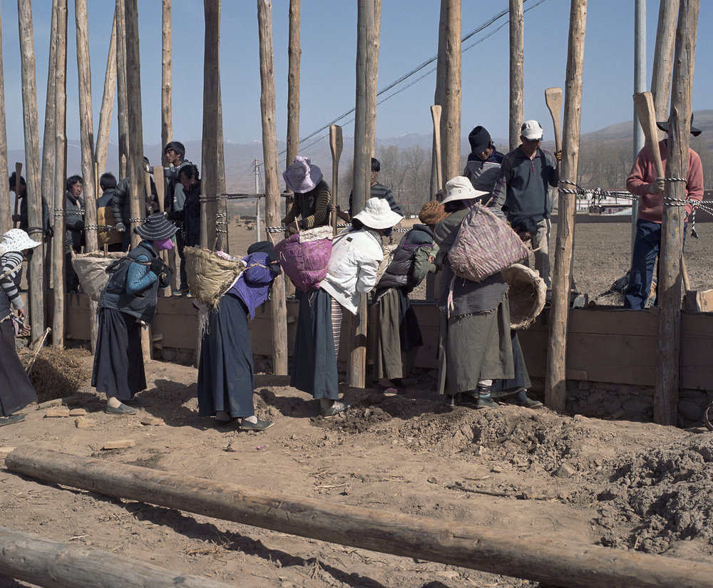 2010, Xianceng - a total village building a mud house together. The women bring the mud. The men stamps that into a wall.