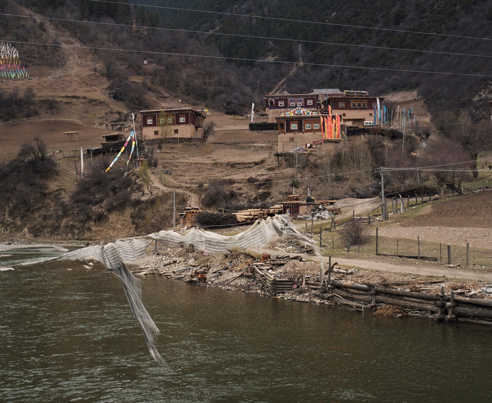 2010, Xinlong - a vilage at the other side of the river. Payer flags on a rope over the water.