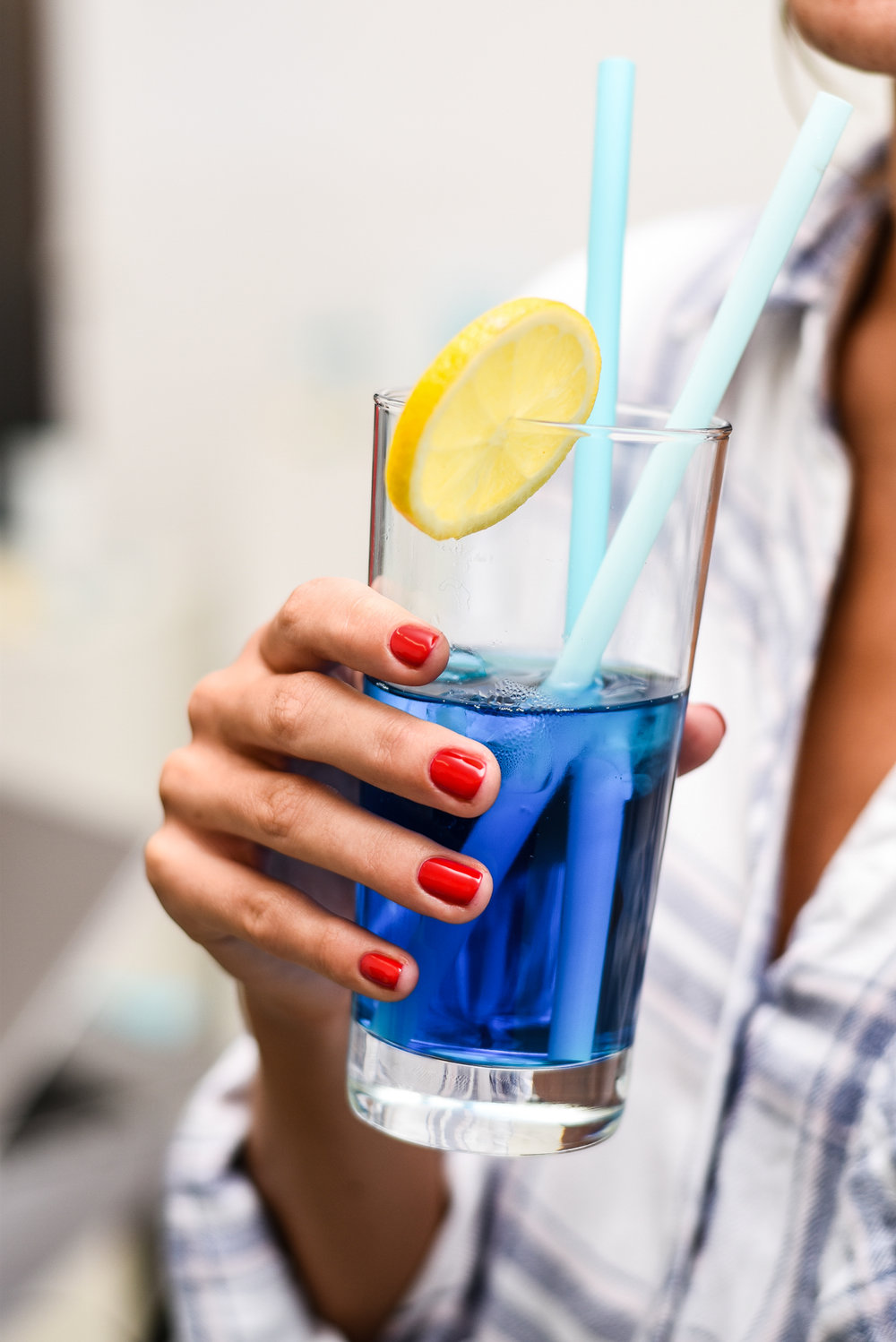 Scandinavian blogger girl with red nails gell manicure drinking a summer cocktail.