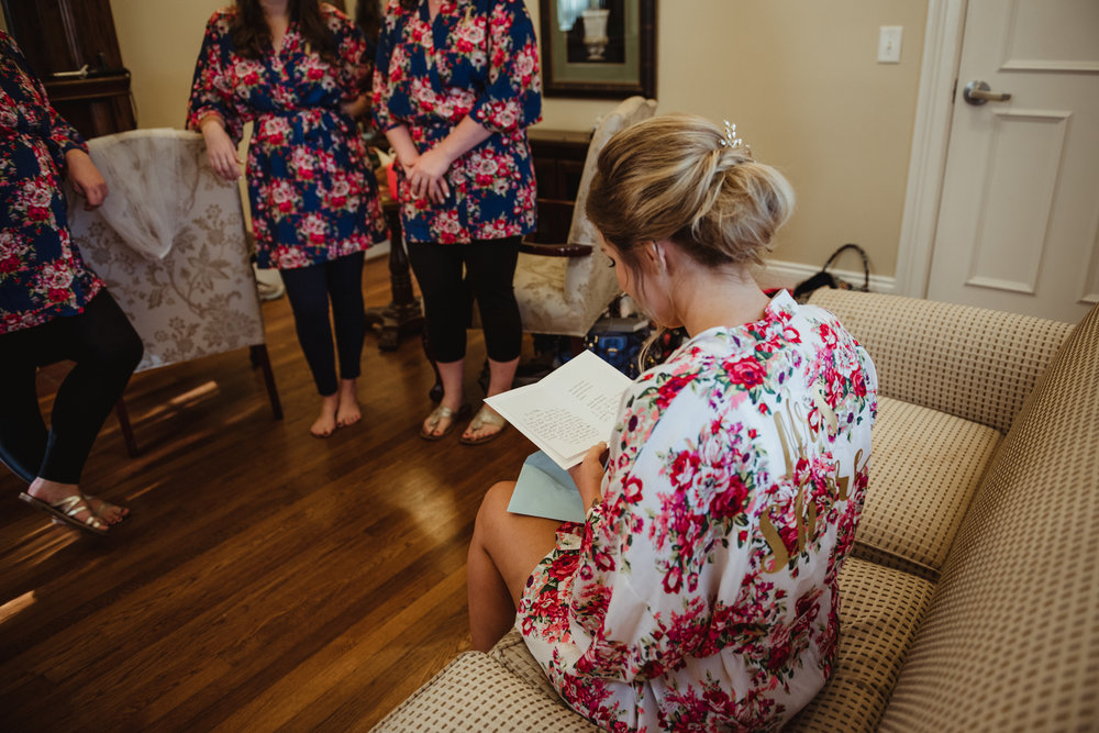 bride-reading-card-from-her-groom-with-her-bridesmaids.jpg