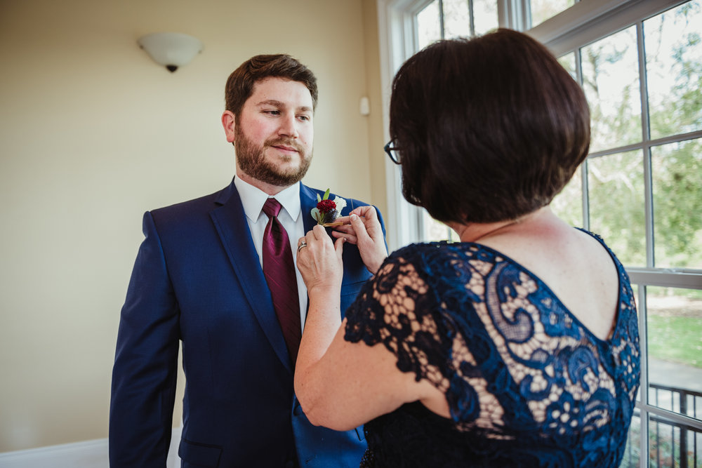 mother-of-the-groom-pinning-on-the-grooms-boutonniere.jpg