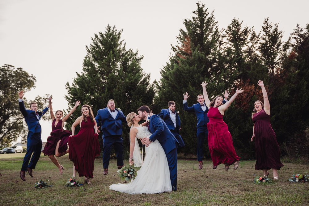 the-bridal-party-jumping-in-the-air-behind-the-bride-and-groom.jpg