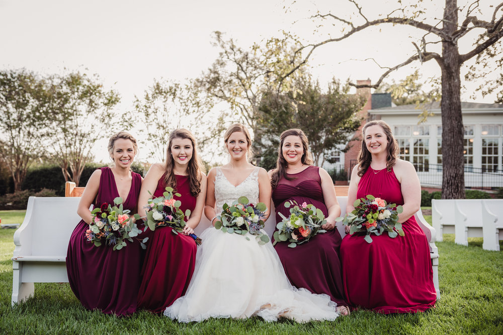 the-bridesmaids-and-bride-sitting-outside-on-a-church-pew.jpg