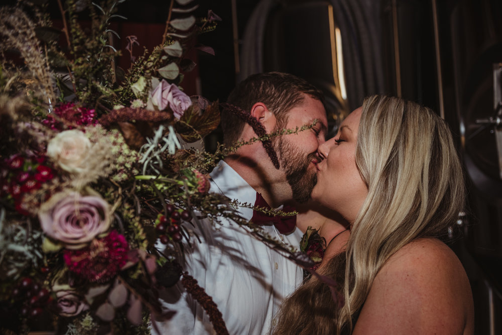 bride-and-groom-portraits-stealing-a-kiss-in-the-brewing-room.jpg