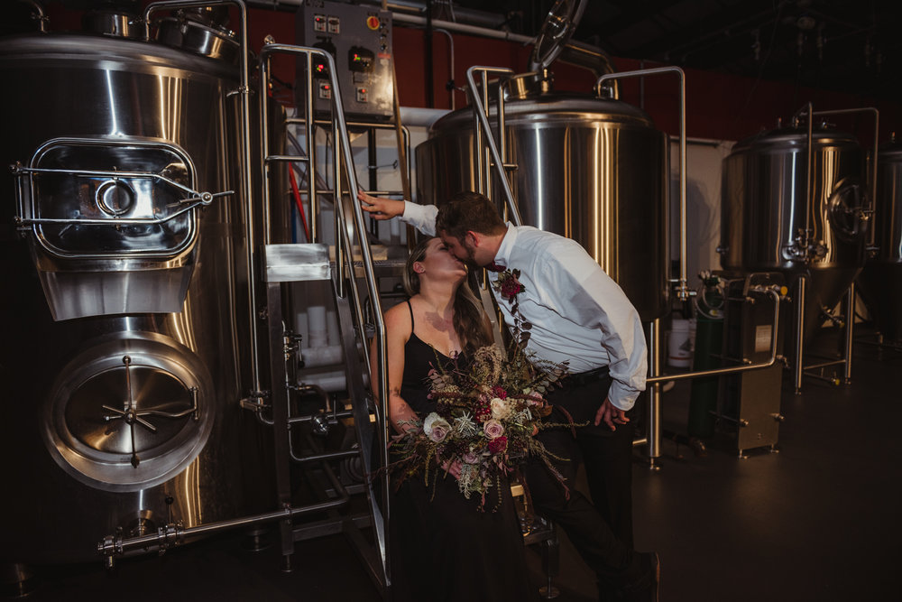 the-bride-and-groom-pose-with-the-brewing-vats-behind-them.jpg