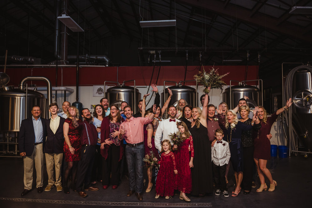 the-entire-wedding-reception-posing-for-pictures-in-the-brewing-room-at-the-brewery.jpg