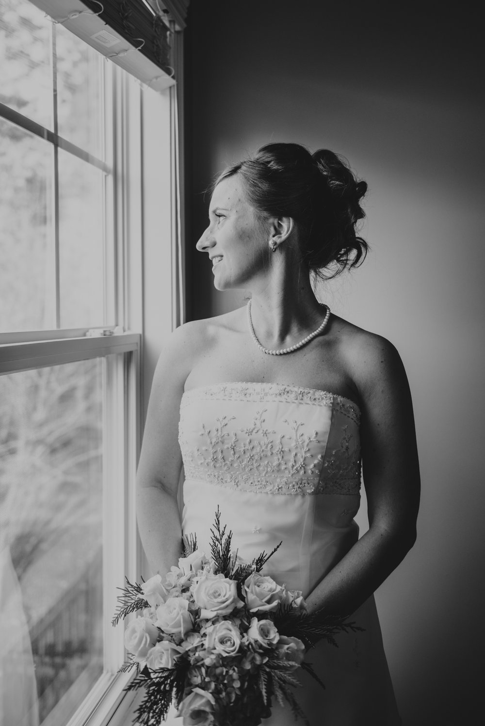 the-bride-looking-out-the-window-eagerly-before-her-intimate-home-wedding-in-Raleigh.jpg