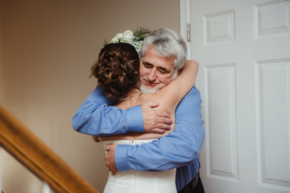 the-bride-hugging-her-dad-when-she-walked-down-the-stairs-to-get-married-at-her-intimate-home-wedding-in-Raleigh.jpg