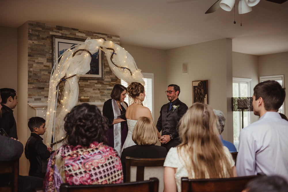 the-groom-looks-at-his-bride-while-she-says-her-vows-at-their-intimate-home-wedding-in-Raleigh.jpg