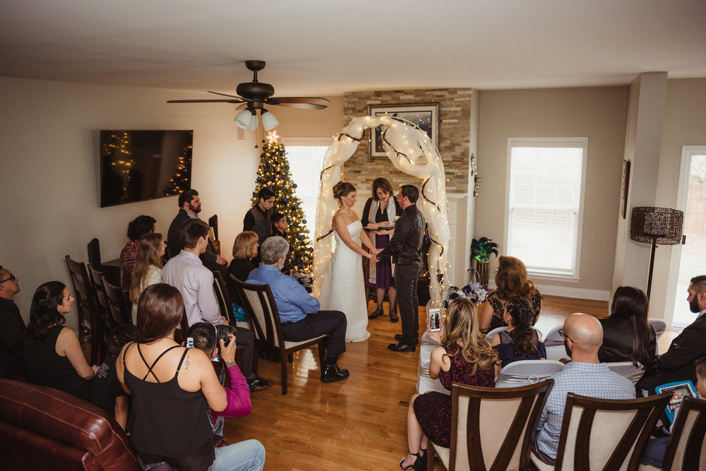 their-families-and-friends-surround-the-bride-and-groom-while-they-exchange-vows-at-their-intimate-home-wedding-in-Raleigh.jpg