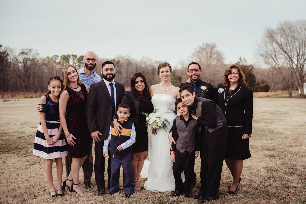 the-bride-and-groom-with-the-grooms-family-in-the-park-in-Raleigh.jpg