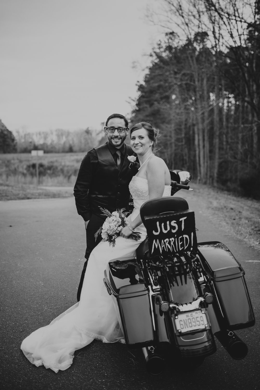 the-bride-and-groom-pose-on-their-bike-after-getting-married-at-an-intimate-home-ceremony-in-raleigh.jpg
