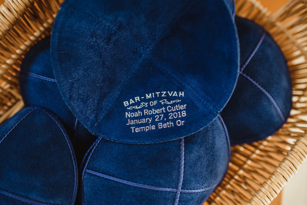 Noah has navy blue kippahs to wear that were inscribed with his name, bar mitzvah ceremony date, and Temple Beth Or.