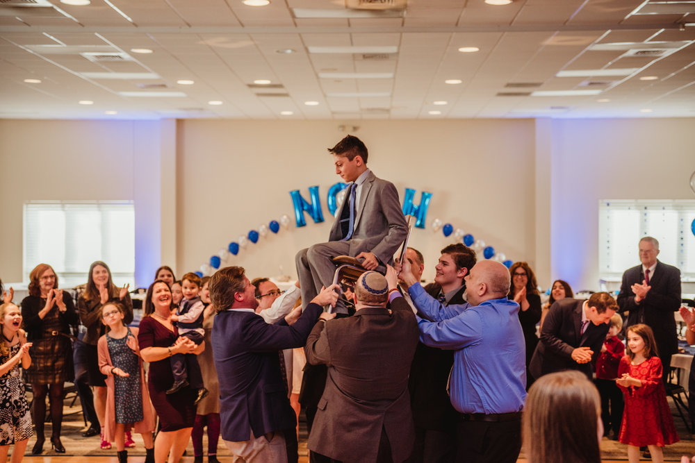 Noah is up high on his chair during the hora part of the bar mitzvah celebration.