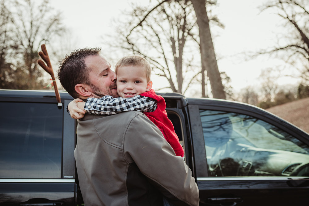 Dad giving his three year old son a hug as they get ready for family photos in Raleigh, North Carolina.
