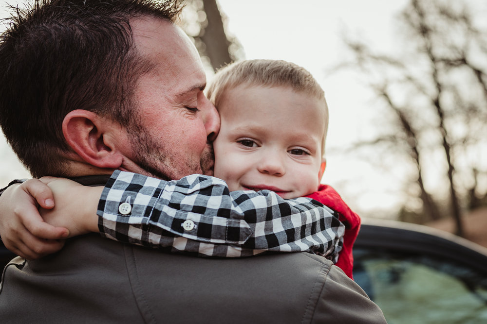 Dad giving his three year old son a kiss as they get ready for family photos at Dorothea Dix Park in Raleigh, North Carolina.