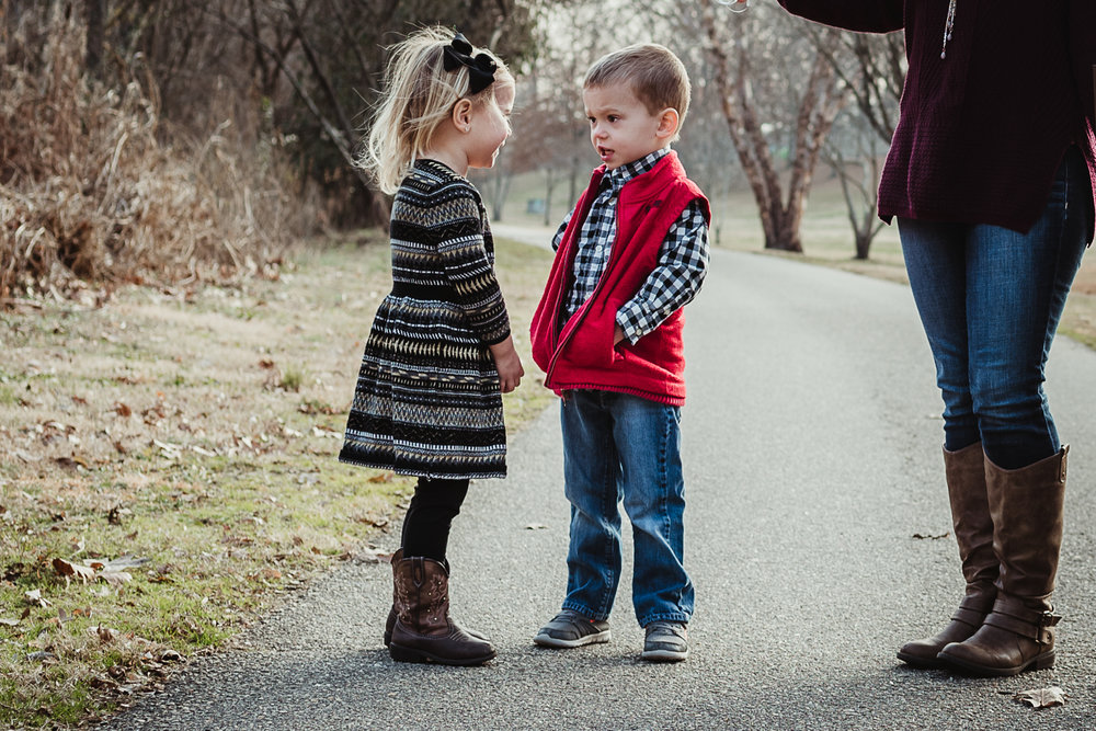 Three year old twin siblings talking to each other before their family pictures in Raleigh, North Carolina.