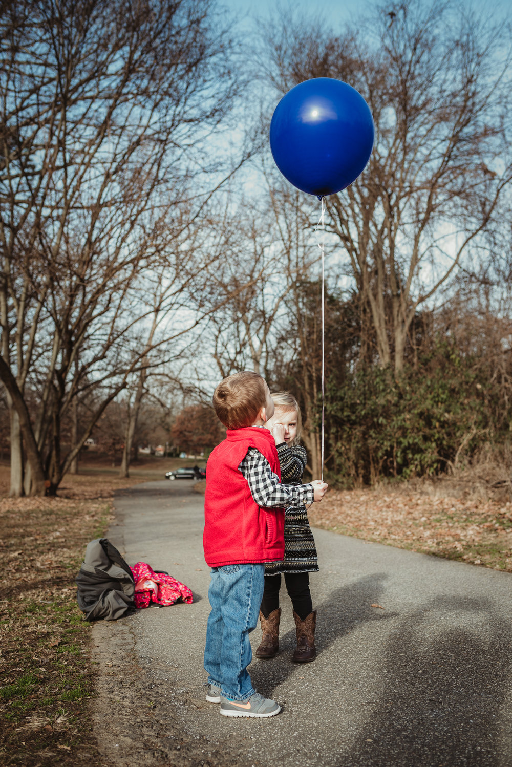 Twin three year old siblings hold onto a blue balloon in Raleigh during their family photos, the blue balloon representing their brother who passed away as a baby.