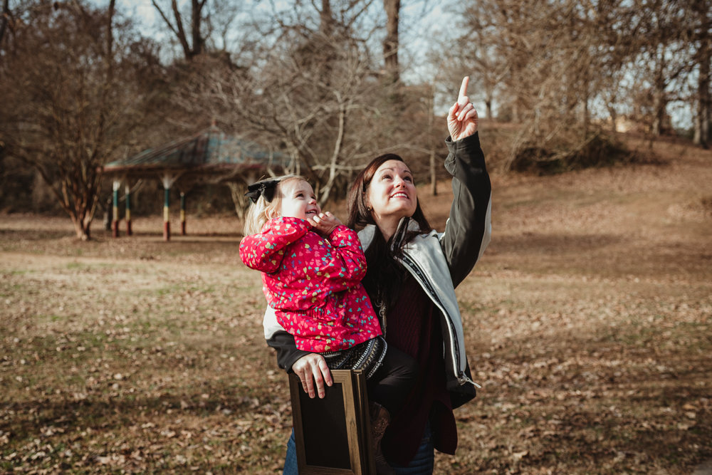 The three year old girl and her Mommy point to the sky during their family session in Raleigh, North Carolina.