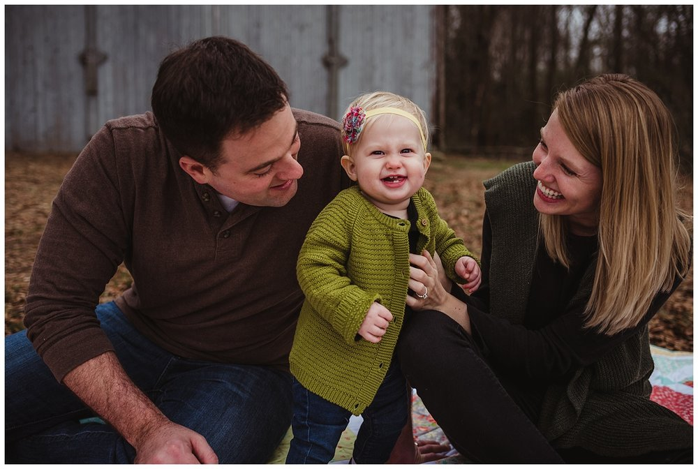 The family of three sits in front of an old barn in Wake Forest, North Carolina while the baby smiles at the camera during their photo session with Rose Trail Images.