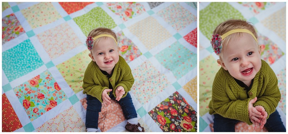 The little girl claps on the handmade quilt during her family photo session in Wake Forest, North Carolina with Rose Trail Images.